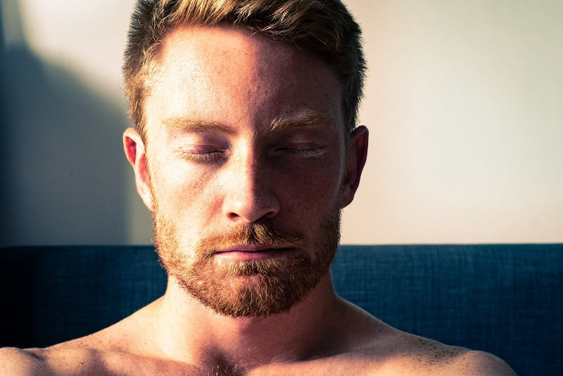 man closing eyes in meditation
