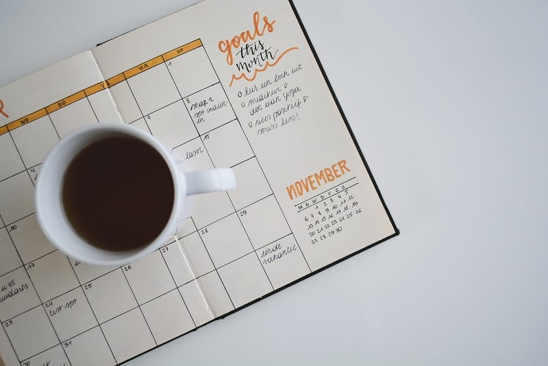 bullet journal planner with mug of coffee