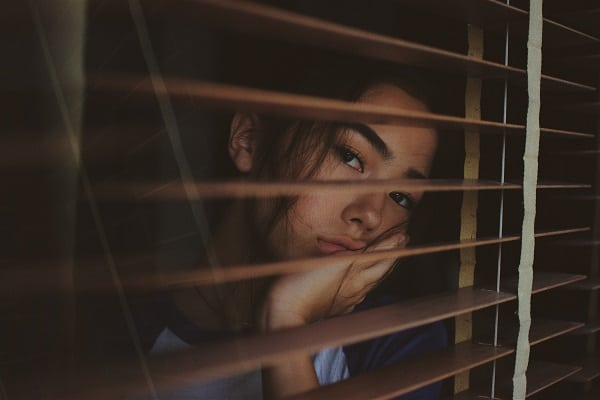 woman looking out of window bored
