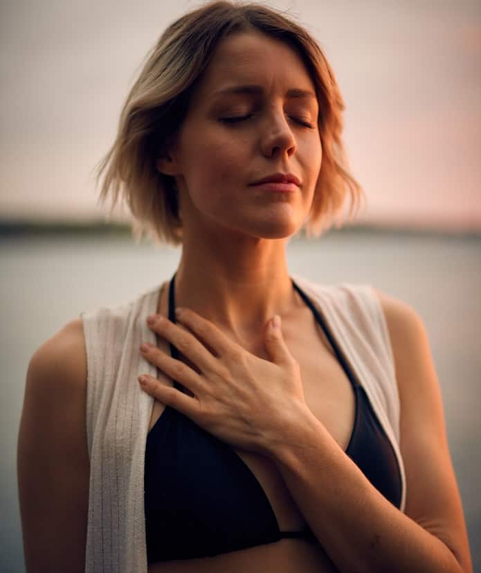 woman breathing and holding chest