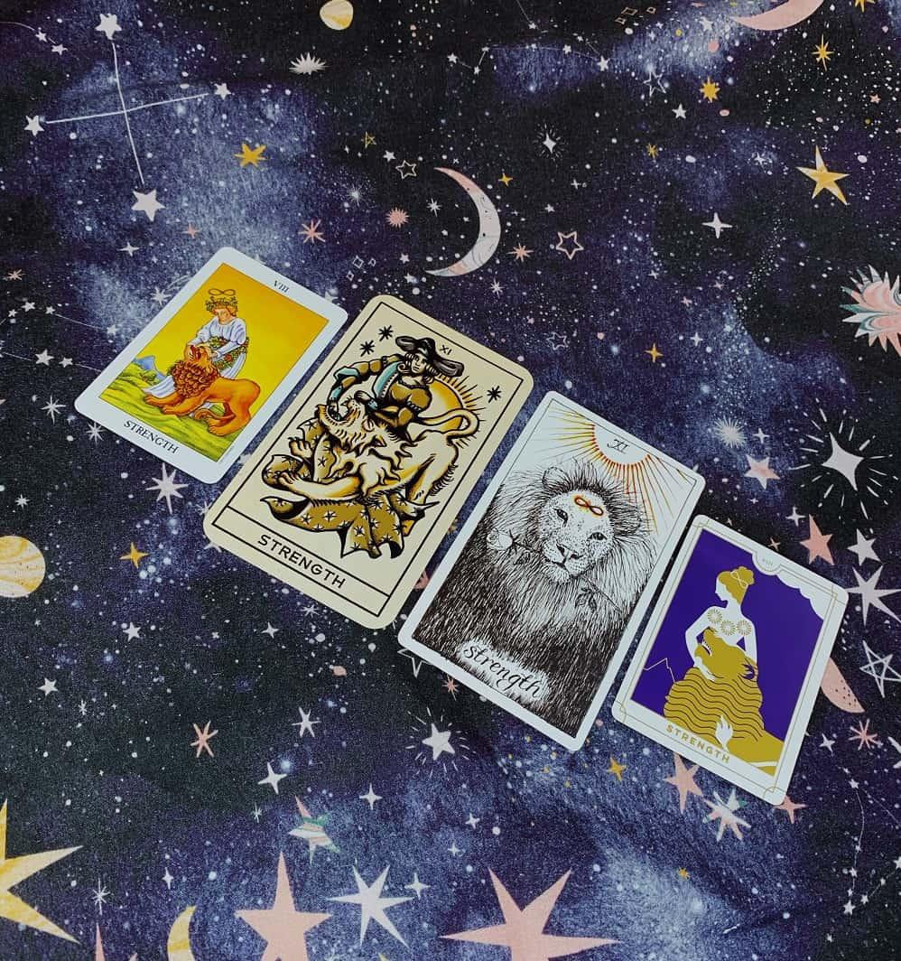 strength tarot card from different decks